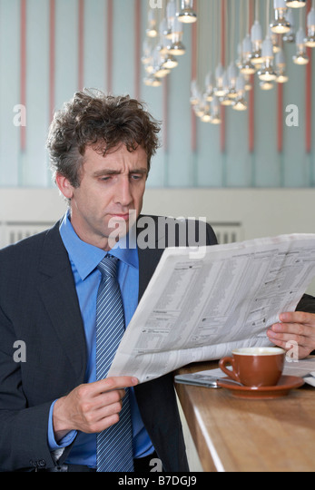 Businessman at bar reading paper, doubt - Stock Image