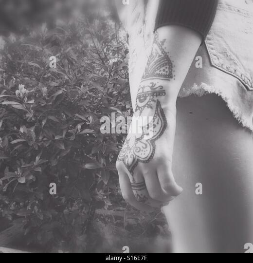 Girl in shorts with henna tattoo on hand - Stock-Bilder