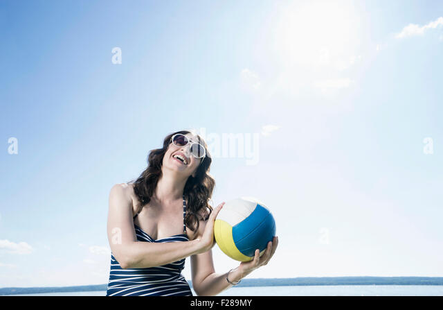 Mature woman playing volleyball on the beach, Bavaria, Germany - Stock Image
