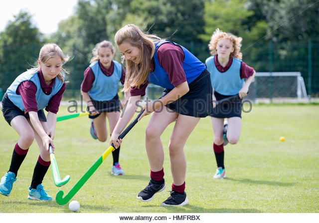 Middle schoolgirls playing field hockey on field in physical education class - Stock-Bilder