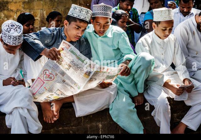 Mumbai India Asian Apollo Bandar Colaba PJ Ramchandani Marg Muslim teen boy friends topi taqiyah cap robe reading - Stock Image