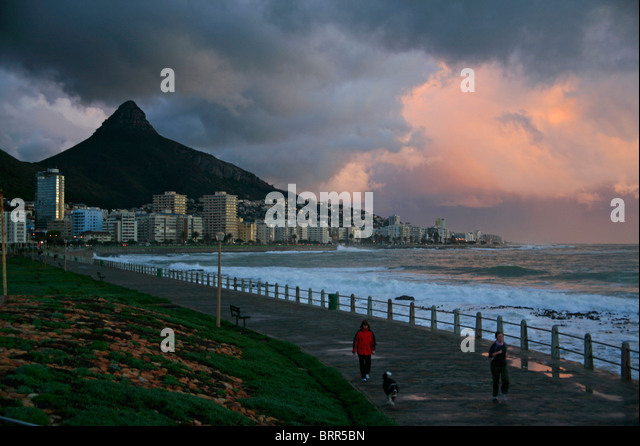 Sea Point promenade with stormy clouds over the Atlantic Ocean and Lion's Head in the background - Stock Image