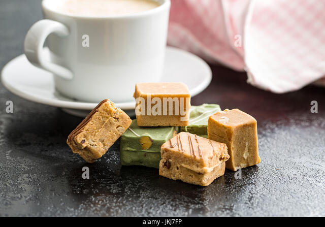 Colorful caramel candies and coffee cup on table. - Stock Image