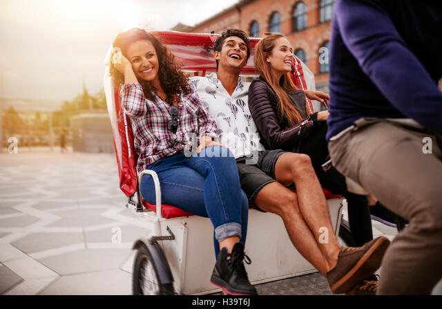 Teenage friends enjoying tricycle ride in the city. Teenagers riding on tricycle on road and smiling. - Stock Image