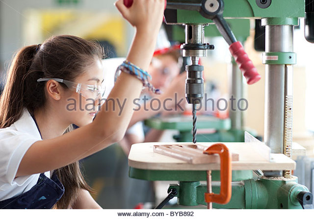 Serious student using drill in vocational school - Stock-Bilder