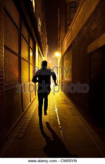 man running down a alley at night - Stock-Bilder