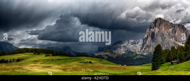storm over the mountains Dolomiti in the summer season with green meadow illuminated of the Sun - Seiser Alm, Trentino - Stock Image