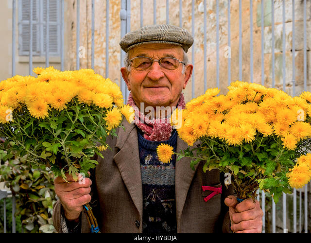 French flower seller holding bunches of yellow chrysanthamums. - Stock Image
