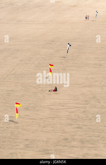 Tourists on Newquay's Fistral Beach in summer sunshine. Beach warning flags. - Stock Image