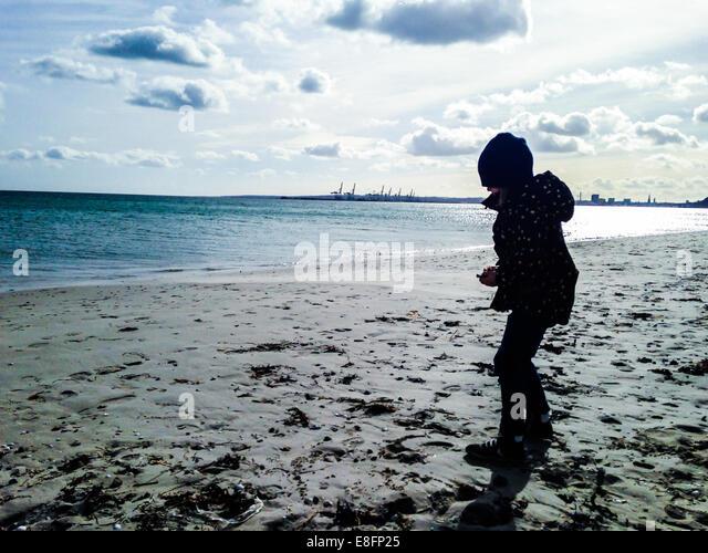 Boy standing on beach - Stock Image