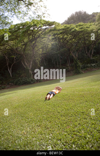 child laying and resting in a grassy field, public park, Honolulu, Hawaii - Stock Image