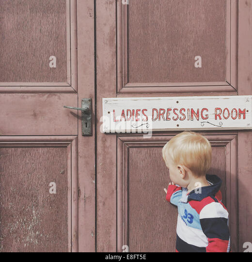 Boy standing outside ladies dressing room - Stock Image