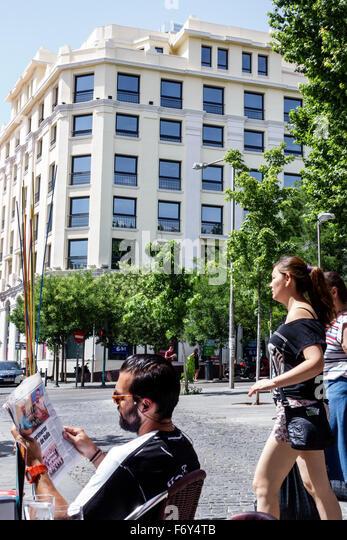 Spain Europe Spanish Hispanic Madrid Centro Chueca Calle Hortaleza Hispanic man reading newspaper woman pedestrian - Stock Image