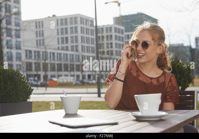 Young woman talking on a mobile phone at sidewalk cafe, Munich, Bavaria, Germany - Stock-Bilder