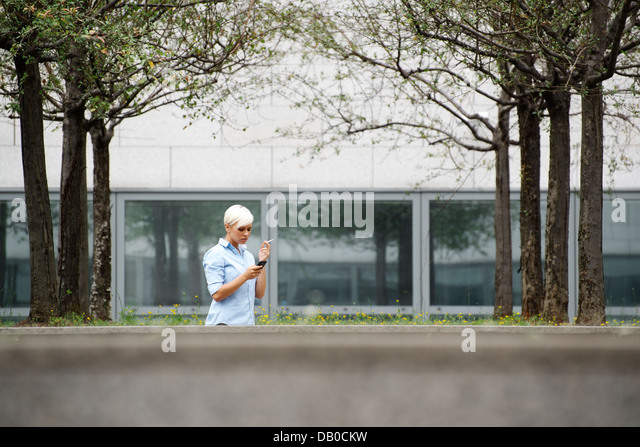 young businesswoman smoking cigarette during break out of office building. Wide shot, copy space - Stock Image