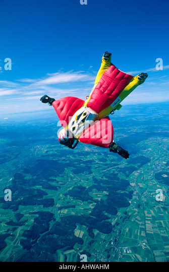 A Skydiver is flying through the skies of Switzerland using a wingsuit during a training jump for a world record - Stock Image