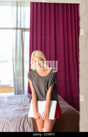 Woman holding laptop in bedroom - Stock-Bilder