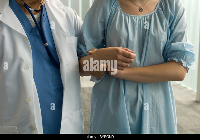 Patient holding on to nurse's arm for support - Stock Image