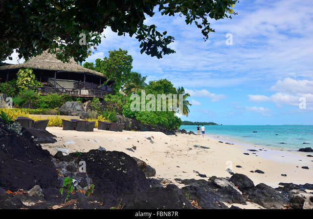 Guests relaxing, strolling  along  the sandy  beach  foreshore at Pacific Resort Aitutaki .Aitutaki Cook Islands - Stock Image