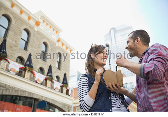 Low angle view of couple eating meal from food truck - Stock Image