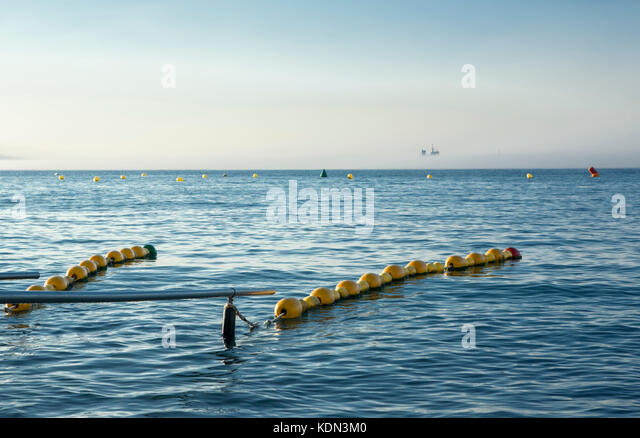 Handrails on beach for disabled people with ship at bottom in the mist. Ceuta, Spain - Stock Image
