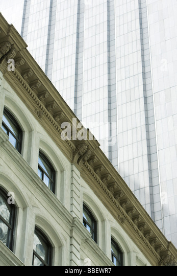 Facade of neoclassical building, modern skyscraper towering above, low angle view - Stock Image