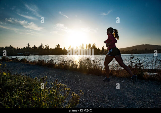 Woman running at sunset on Whiffen Spit - Quimper Park in Sooke, Vancouver Island, British Columbia, Canada - Stock Image
