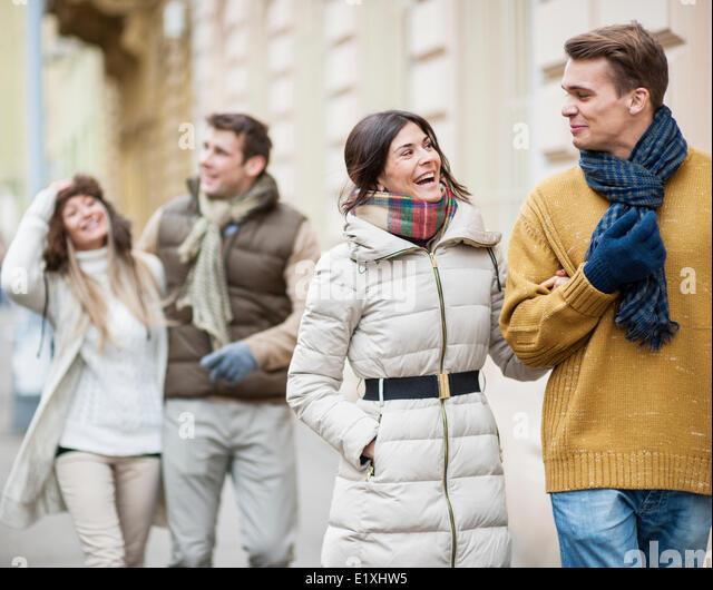Happy couples in warm clothing enjoying vacation - Stock Image