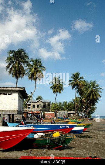 Grenada caribbean island colorful fishing boats on beach palm trees blue sky southern caribbean background - Stock Image