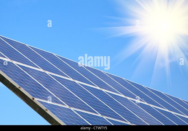 Solar panel against blue sky with sun sunlight - Stock Image