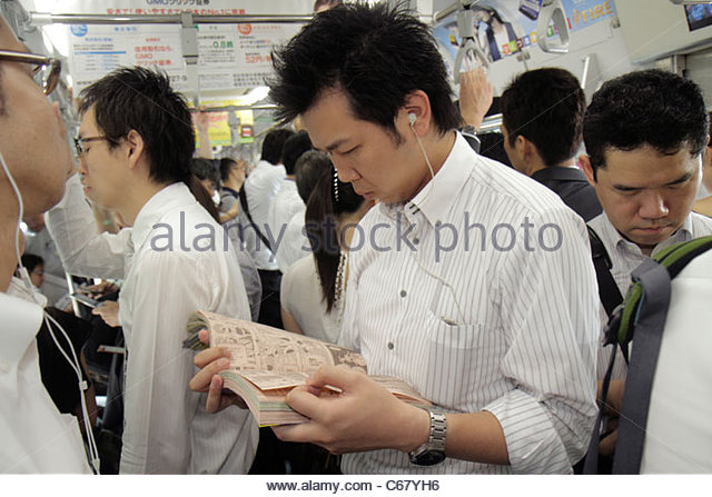 Tokyo Japan Yurakucho JR Yurakucho Station Yamanote Line Asian man crowded standing commuters train car strap holders - Stock Image