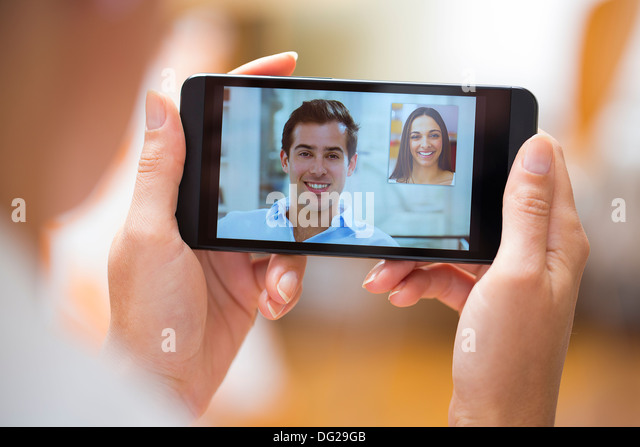 Woman chatting with her friend on smartphone at home - Stock-Bilder