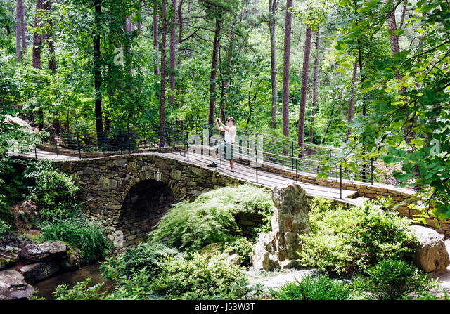 Arkansas Hot Springs Garvan Woodland Gardens Full Moon Bridge man take picture camera Joy Manning Scott stone self - Stock Image