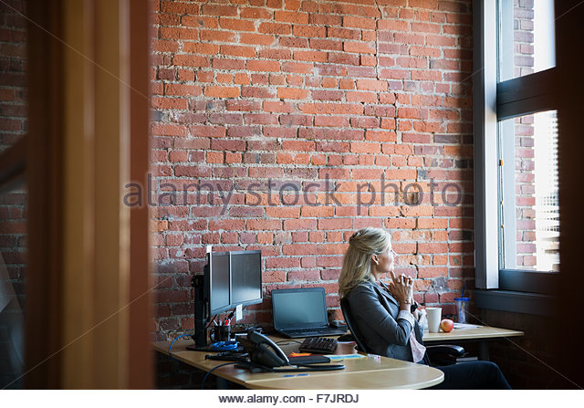 Pensive businesswoman looking out office window - Stock Image