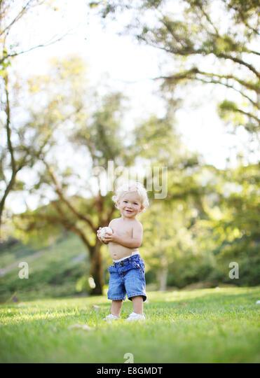 Toddler holding baseball - Stock Image