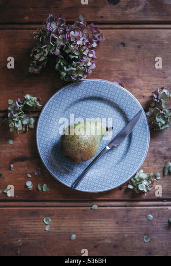 Pear on a dessert plate - Stock Image