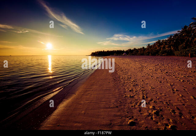 Footprints on the tropical beach at sunset with sun over ocean - Stock Image