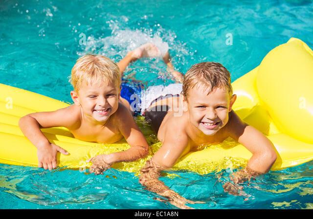 Young Kids Having Fun in Swimming Pool on Yellow Raft. Summer Vacation Fun. - Stock Image