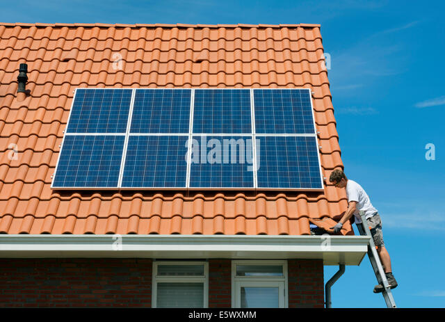 Worker checking installation of solar panels on roof of new home, Netherlands - Stock Image
