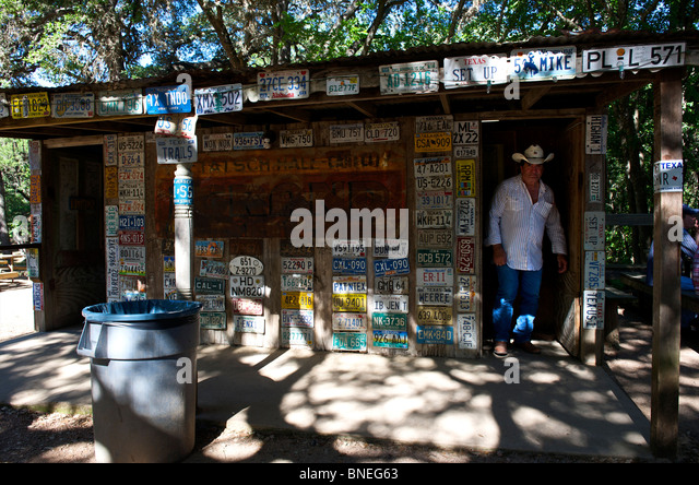 Man coming out of restroom with license plates, Luckenbach, Hill country, Texas, USA - Stock Image
