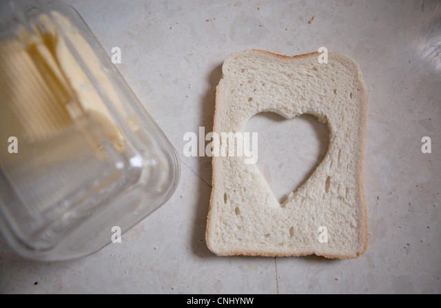 Heart shaped cut out from slice of bread - Stock Image