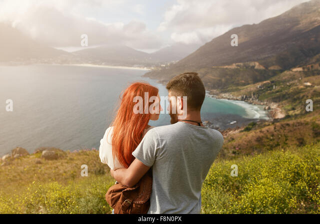 Romantic young couple embracing and looking at each other on a sunny day outdoors. Man and woman looking into each - Stock Image