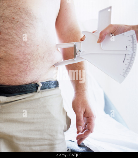 Body fat assessment. 39-year-old overweightman having his body fat measured. - Stock Image