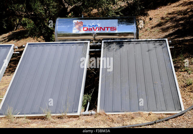 Solar water heaters on the ground beside a house in the small Greek village of Giolova in the Peloponnese. - Stock Image