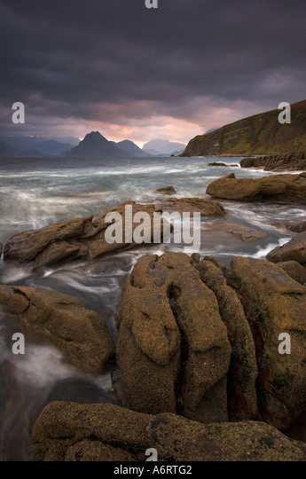 The ancient geology of Skye lies broken on the beach at Elgol, battered by the ocean.  An ominmous sky hangs over - Stock Image