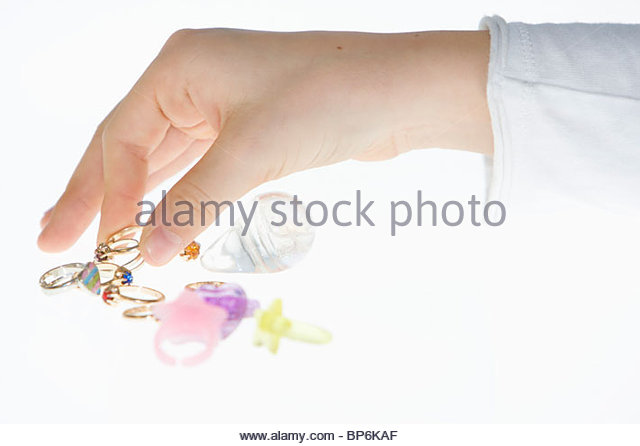 A young girl looking at a selection of rings, close-up of hand - Stock Image
