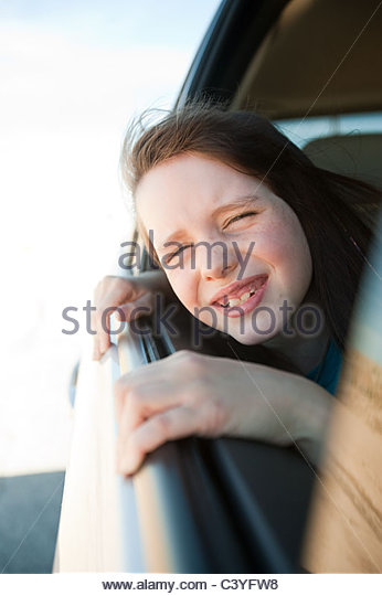 Girl leaning out of car window - Stock Image