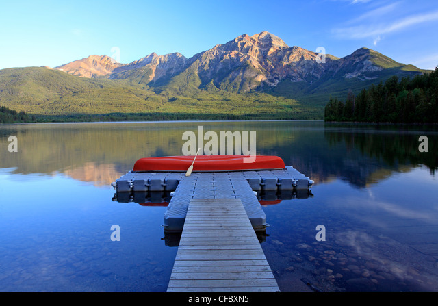 Red canoe on dock at Pyramid Lake with Pyramid mountain, Jasper National Park, Alberta, Canada. - Stock Image