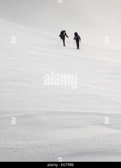 two men with heavy backpacks climbing a mountain slope on snowshoes in  winter. Huldraheimen, Gausdal Westfjel, - Stock Image