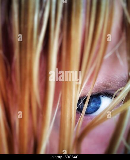 Girl with blue eyes peering out from behind curtain of wet blond hair - Stock Image
